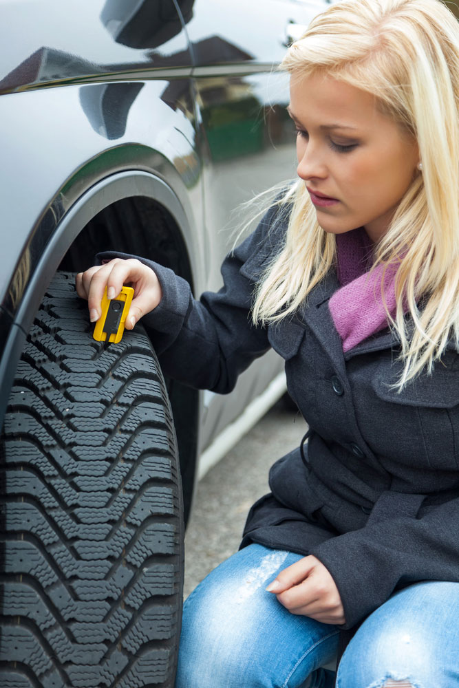 checking tyre tread depth by blonde girl